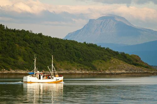 Bilde av gammel fiskebåt av tre på havet ved Harstad