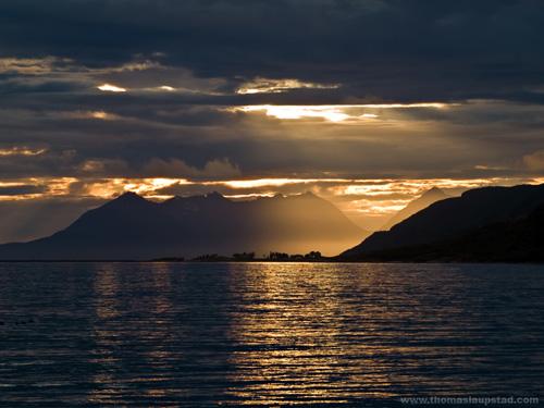 Bilde av landsby i havet Nord Norge med midnattssolnedgang som bakgrunn