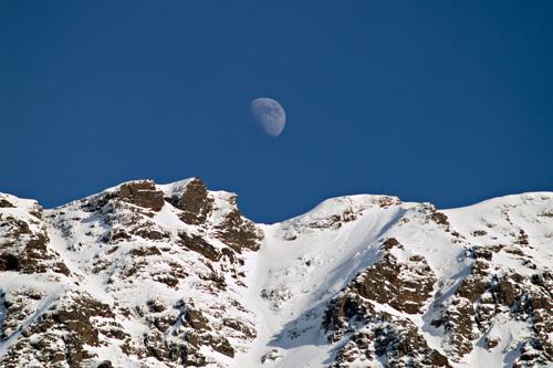 Foto av månen over snødekt fjell i Nord Norge