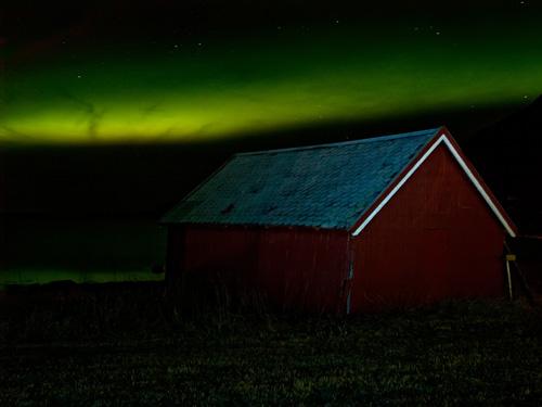 Bilde av nordlys over naust i Nord Norge