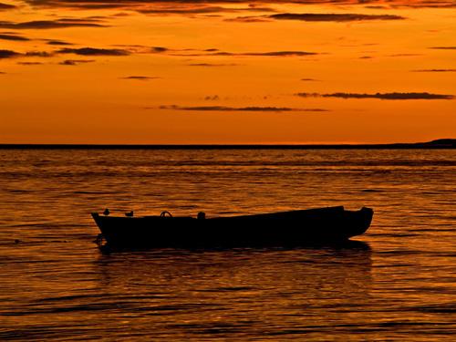 Bilde av gammel robåt og vakker solnedgang i Nord Norge