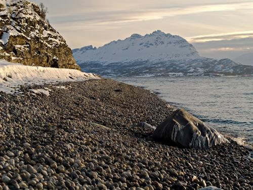 Bilde fra rullesteinfjære med snødekt fjell som bakgrunn