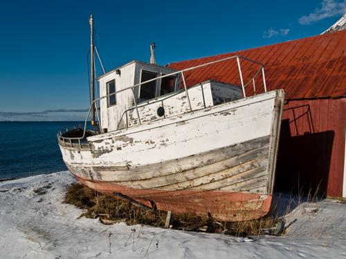 Bilde av gammel forfallen sjark på land i Nord-Norge