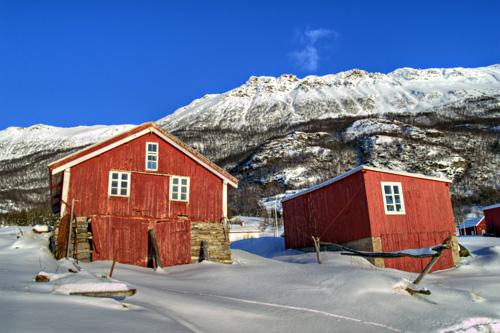 Bilde av to gamle naust og snødekte fjell i Nord Norge